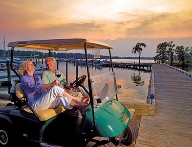Couple on golf cart on dock at marina at sunset at Albemarle Plantation in Hertford, North Carolina