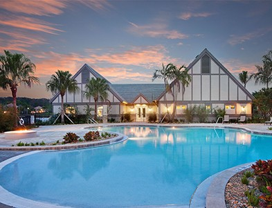 Minto at TwinEagles – Florida Coastal Communities - Sunset at swimming pool and clubhouse at TwinEagles in Naples, Florida