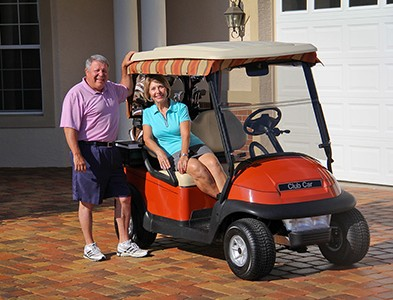 Couple golfing with golf cart at On Top of the World Communities in Ocala, Florida