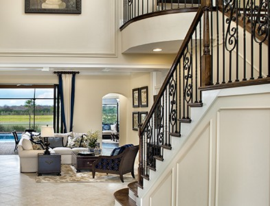 Minto at TwinEagles – Florida Coastal Communities - House interior stairway and living room at TwinEagles in Naples, Florida